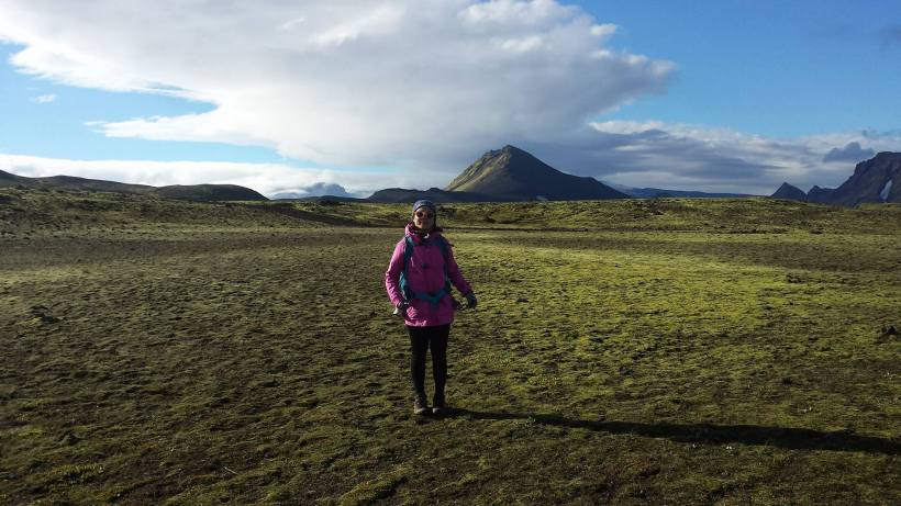 Girl in pink in Iceland on a wide green land with mountains in the back