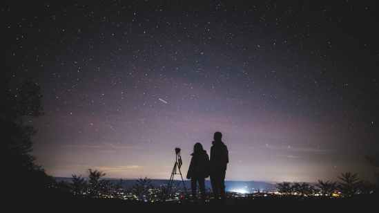 silhouette of two person standing during nighttime