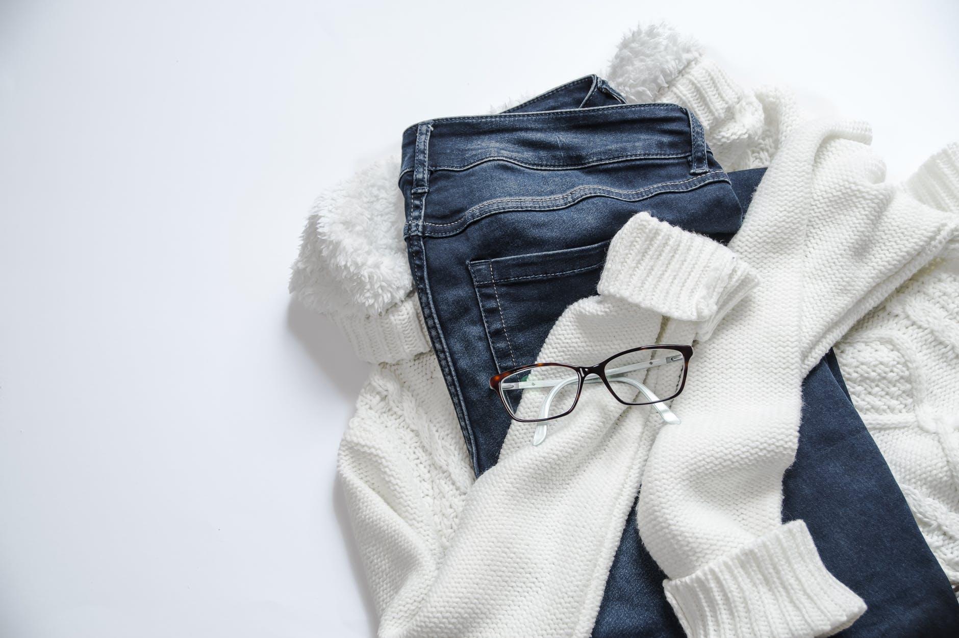 black framed eyeglasses on white jacket and blue denim bottoms